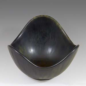 A small freeform bowl with a brown haresfur glaze  designed by Gunnar Nylund for Rorstrand of Sweden