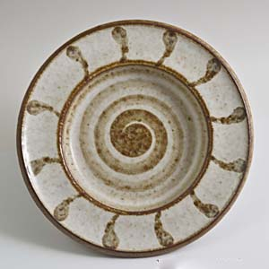 designed by maria philippi for soholm a small bowl/tray with a spiral pattern in brown on a cream colored background